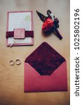 Small photo of envelope invitation budonier wedding rings on the table in hotel decorated with feathers in claret color