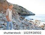 young man on rocky beach summer ... | Shutterstock . vector #1025928502