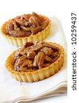 Little pecan tarts.  A luscious nutty dessert treat.  Shallow focus. - stock photo