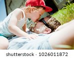 a sweet child kisses his father ... | Shutterstock . vector #1026011872