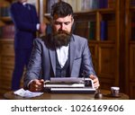 Small photo of Writing and literature concept. Writer working on new book with friend and bookshelves on background. Author types novel or poem. Man with beard and busy face sit in library and work with typewriter.