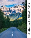 Dolomite Alps in Italy. Beautiful day. The road passes in the coniferous forests at the foot of limestone and dolomite rocks. The concept of active and car tourism - stock photo