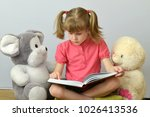 child reads a book of soft toys. | Shutterstock . vector #1026413536