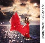 Beautiful Girl in Red Dress Standing on Ocean Rocks - stock photo