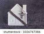 Small photo of Small white house, chain and a decorative key on a dark background. Concept - risks, lose property, seize, mortgage.