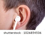 Small photo of Young caucasian teenage boy's left ear with an ear bud headphone