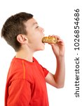 Young caucasian teenage boy eating a sausage roll - stock photo