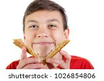 Young caucasian teenage boy with the crusts of a sandwich - stock photo