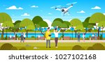 couple flying drone in park man ... | Shutterstock .eps vector #1027102168