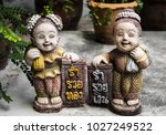 Small photo of Old Statue of the boys and girls wear thai Dress are standing smiling with green leaves, tree pots on white cement floor with mold in the house. Thailand text is mean rich gold and rich money, vintage
