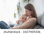 young mother  holding her sick... | Shutterstock . vector #1027405336