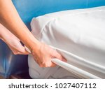woman is putting the bedding... | Shutterstock . vector #1027407112