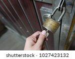 unlocking padlock on the gate... | Shutterstock . vector #1027423132