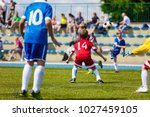 young boys playing soccer... | Shutterstock . vector #1027459105