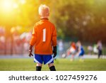 Small photo of Young Soccer Goalie Goalkeeper. Young Boy Soccer Goalie. Soccer Game on Sunny Summer Day. Sport activities for children.. Football Match in the Backround. Youth Sport Wallpaper.