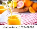 pouring orange juice in to... | Shutterstock . vector #1027478608