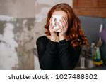 Small photo of Bashful young woman hiding behind her mug of coffee as she holds it in front of her face with both hands