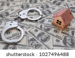 Small photo of iron handcuffs, a house made of wood on a background of American dollar bills. illegal sale of property. swindle. economic crimes.