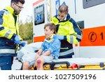 Small photo of Emergency medics taking care of injured boy with whiplash