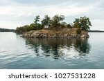 tiny house in a tiny island  | Shutterstock . vector #1027531228