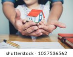 hands holding small house after ... | Shutterstock . vector #1027536562