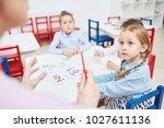 attentive lementary schoolgirl... | Shutterstock . vector #1027611136