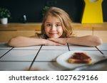 portrait of little girl eating... | Shutterstock . vector #1027629166