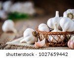 garlic bulbs in wooden basket... | Shutterstock . vector #1027659442