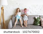 two mischievous little girls... | Shutterstock . vector #1027670002