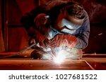 welder working at the factory ... | Shutterstock . vector #1027681522
