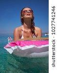 Small photo of Happy woman in bikini lying on air bed in sea or ocean