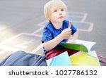 cute blond boy doing homework... | Shutterstock . vector #1027786132