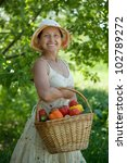 mature woman with basket of harvested vegetables - stock photo
