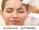 young woman undergoing eyebrow... | Shutterstock . vector #1027984882