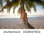 woman rests at the palm tree... | Shutterstock . vector #1028037832