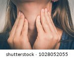 woman with throat sore is... | Shutterstock . vector #1028052055