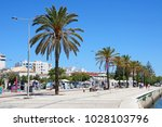 Small photo of PORTIMAO, PORTUGAL - JUNE 7, 2017 - Tree lined promenade alongside the Arade River with city buildings to the rear and people going about their business, Portimao, Algarve, Portugal, June 7, 2017.