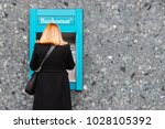 Small photo of GOTHENBURG, SWEDEN - FEBRUARY 16, 2018: Woman making a withdraw in a cash automat in Gothenburg city centre, Sweden