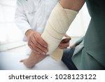 orthopedist applying bandage... | Shutterstock . vector #1028123122