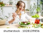 young woman eating healthy food ... | Shutterstock . vector #1028139856