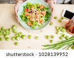 holding a plate with healthy... | Shutterstock . vector #1028139952