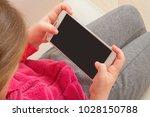little girl holding smartphone...   Shutterstock . vector #1028150788