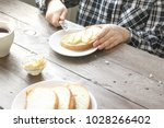 male hands spreading butter on... | Shutterstock . vector #1028266402