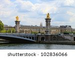 At the bridge ends are gilded with gold statues perched on pillars 17 meters high. - stock photo