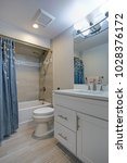 Small photo of Perfectly designed bathroom with white vanity cabinet, tub and shower combo accented with grey marble tiles surround and blue curtain.