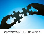 hands connecting two puzzle... | Shutterstock . vector #1028498446
