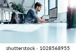 young man sitting in office and ... | Shutterstock . vector #1028568955