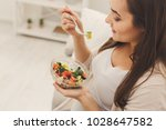 young pregnant woman eating... | Shutterstock . vector #1028647582
