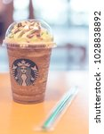 Small photo of December 13, 2017. Bangkok, Thailand: Starbucks Grande frappuccino mocha blened coffee on wooden table