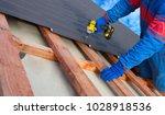 man worker uses a power drill...   Shutterstock . vector #1028918536